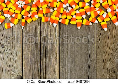 Halloween candy corn top border against wood - csp49487896
