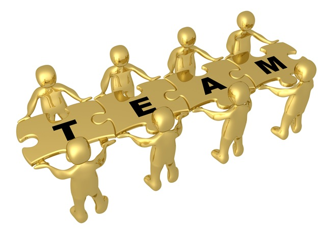 Team Of 8 Gold People Holding Up Connected Pieces To A Colorful Puzzle